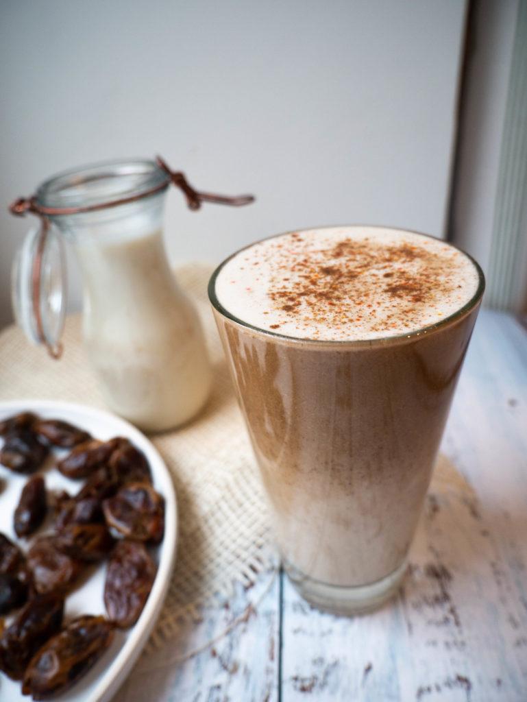 Zdjęcie domowej daktylowej latte z cynamonem na wierzchu.